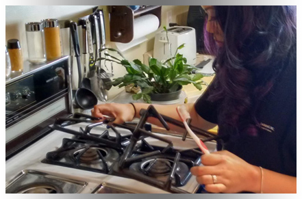 Curly-haired cleaning professional scrubbing oven burner with toothbrush