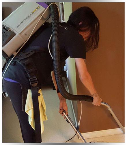 Professional cleaner using HEPA filter backpack vacuum on trim