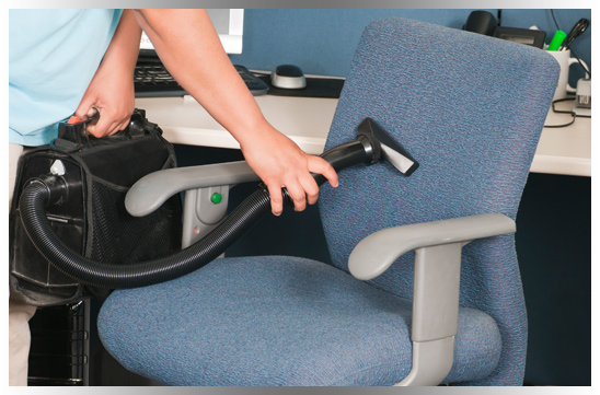 Professional commercial cleaner cleaning office chair with portable vacuum
