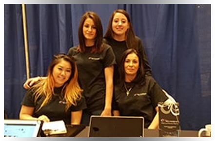 Group of cleaning professionals behind desk at charity event