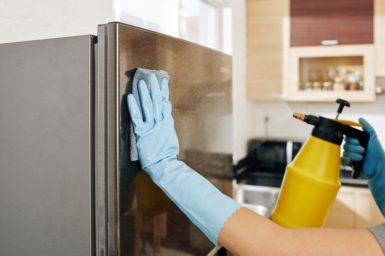 Spraying stainless steel refrigerator with DIY disinfectant spray