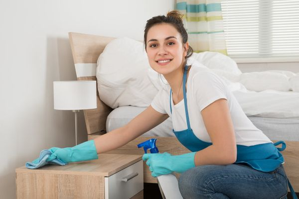 Smiling domestic engineer wiping dust off nightstand in Mississauga apartment
