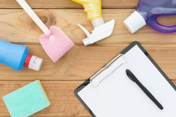 Cleaning supplies and moving cleaning checklist on wooden table